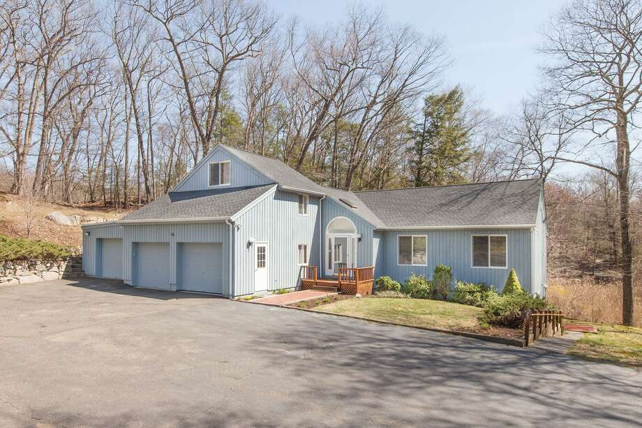 The slate blue contemporary house at 15 Mountain Road is on a one-acre property surrounded by forested ridges creating a private sanctuary and yet very convenient to Danbury Road (Route 7).