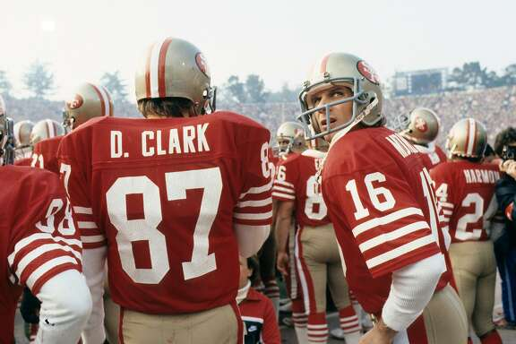 STANFORD, CA - JANUARY 20:  Quarterback Joe Montana #16 of the San Francisco 49ers stands next to receiver Dwight Clark #87 prior to player introductions before the start of Super Bowl XIX against the Miami Dolphins at Stanford Stadium on January 20, 1985 in Stanford, California.  The 49ers defeated the Dolphins 38-16.  (Photo by George Gojkovich/Getty Images)
