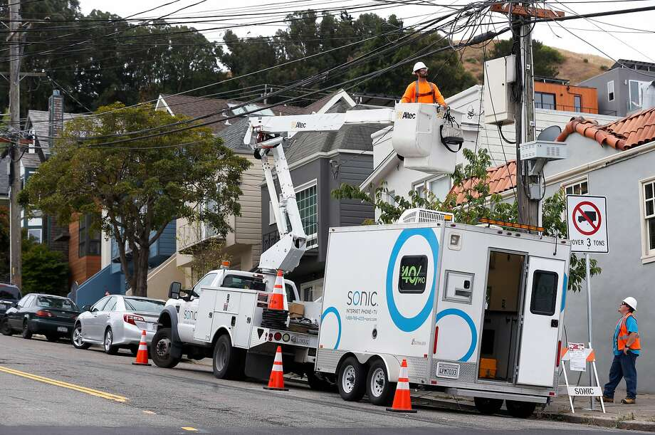 Carlos Contreras and Josh Bishop (lower right) completes the installation of fiberoptic equipment into a utility pole junction box for Sonic's gigabit fiber internet service on Alabama Street near Precita Park in San Francisco, Calif. on Thursday, June 1, 2017. Photo: Paul Chinn, The Chronicle