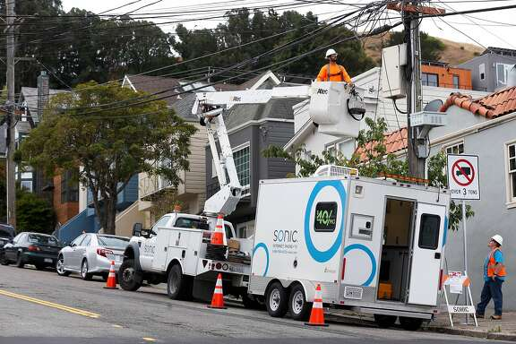 Carlos Contreras and Josh Bishop (lower right) completes the installation of fiberoptic equipment into a utility pole junction box for Sonic's gigabit fiber internet service on Alabama Street near Precita Park in San Francisco, Calif. on Thursday, June 1, 2017.