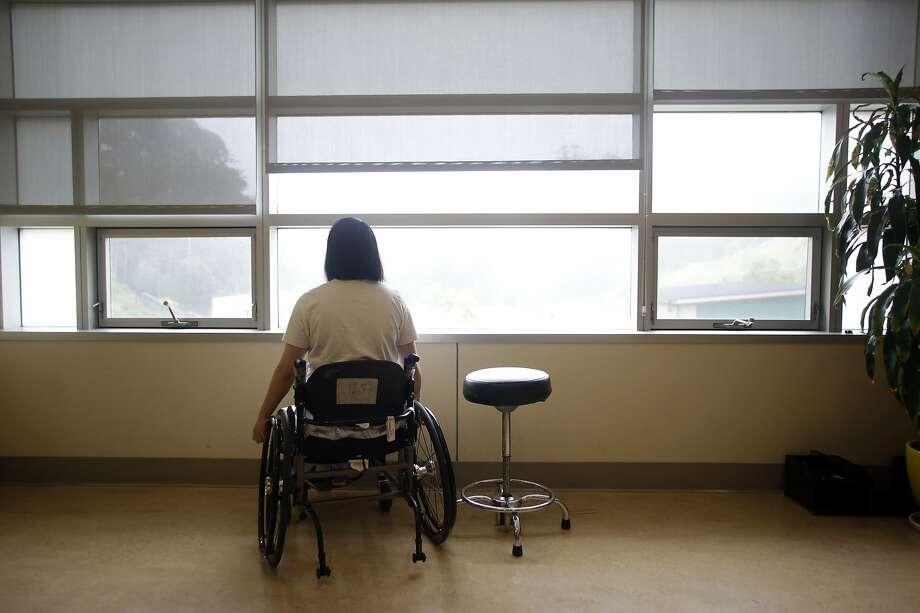 Emma Zhou gazes out a window of a room as she waits to check in with Dr. Nancy Fung, Laguna Honda Hospital rehabilitation specialist. Photo: Lea Suzuki, The Chronicle