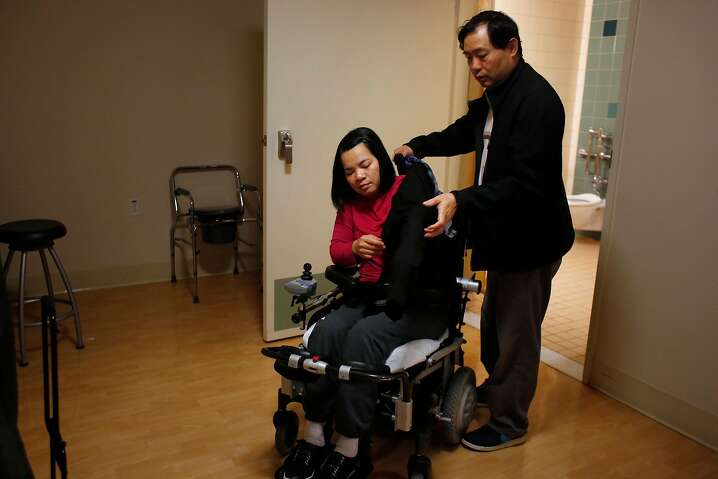 Tony Tan (right) places a jacket over Emma Zhou's shoulders as they prepare to leave Laguna Honda Hospital and Rehabilitation Center for an outting to the �Myoshinji Temple with their family on Sunday, March 19, 2017 in San Francisco, Calif.