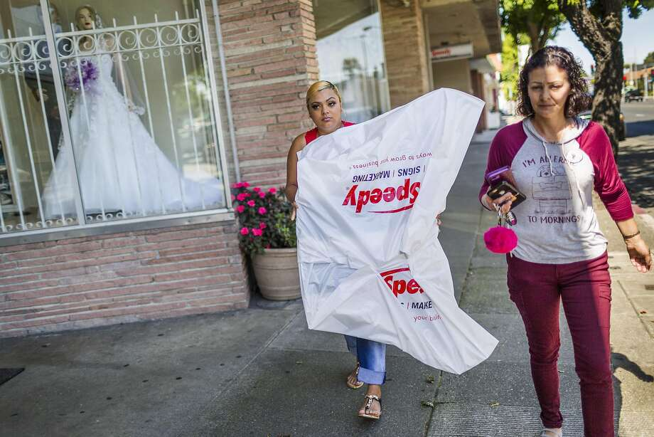 Alicia Saddler, center, carries a cutout of her brother Angel Ramos, as she walks back to her car with her mother Annice Evans, June 1, 2017 in Vallejo, CA. Evans and Saddler were picking up a cutout of Ramos at a print shop for his birthday. If Ramos were alive, he would be 22 years old on June 3. However, he was shot by Vallejo police during a January scuffle outside the home he shared with his mother, sister and other family members. Photo: Eric Kayne, Special To The Chronicle