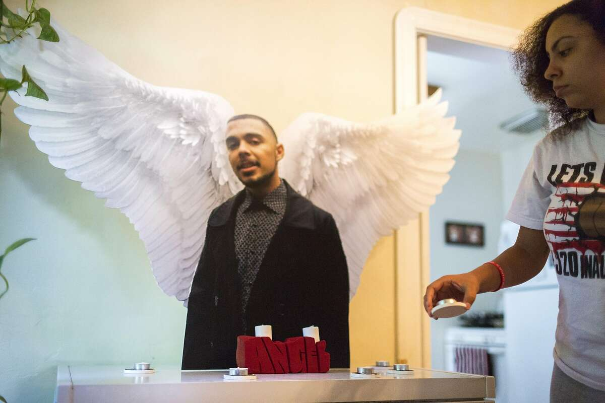Antionette Saddler, sister of Angel Ramos, in cutout, places candles in front of his image June 1, 2017 in Vallejo, CA.
