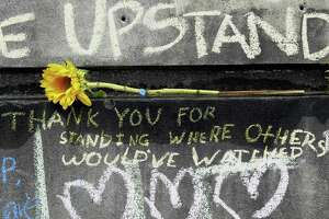 A flower and message are shown at a memorial in Portland, OR on May 30 for the victims who were fatally stabbed while trying to stop a man from shouting anti-Muslim insults at two young women on a Portland light-rail train.