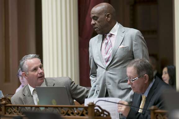 State Sen. Steven Bradford, D-Gardena, center, talks with Republican Senators Anthony Cannella, of Ceres, left, and Tom Berryhill, of Twain Harte, at the Capitol, Thursday, June 1, 2017, in Sacramento, Calif. Lawmakers have until the end of this week to meet a deadline to have their bills passed out of the house of origination. (AP Photo/Rich Pedroncelli)