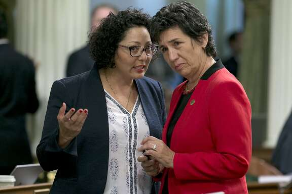 Democratic Assemblywomen, Cristina Garcia of Bell Gardens, left, and Susan Talamantes Eggman, of Stockton, confer during the Assembly session Thursday, June 1, 2017, in Sacramento, Calif. Lawmakers have until the end of this week to meet a deadline to have their bills passed out of the house of origination. (AP Photo/Rich Pedroncelli)