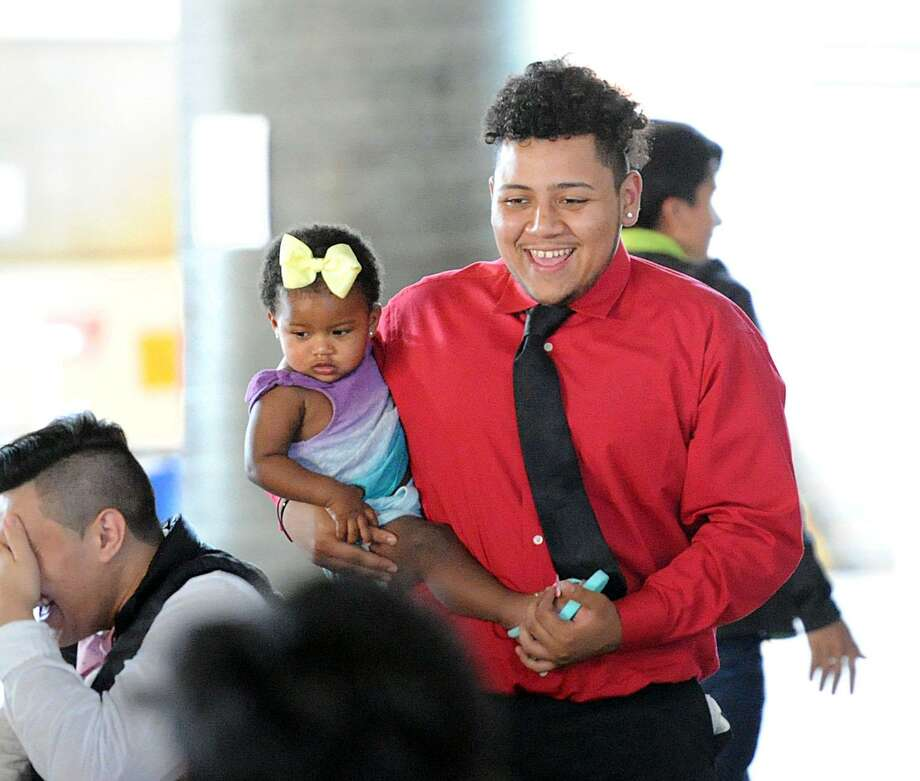 Holding his one-year-old niece Aileen Cevallos, Jacob Hernandez, 18, smiles during his Greenwich High School AVID Graduation Ceremony in the student center at Greenwich High School, Conn., Thursday, June 1, 2017. Hernandez said he will be attending Eastern Connecticut State University in the fall. The Advancement Via Individual Determination program (AVID), targets students in the academic middle and mentors them throughout their school years to prepare them to succeed in college. Photo: Bob Luckey Jr. / Hearst Connecticut Media / Greenwich Time