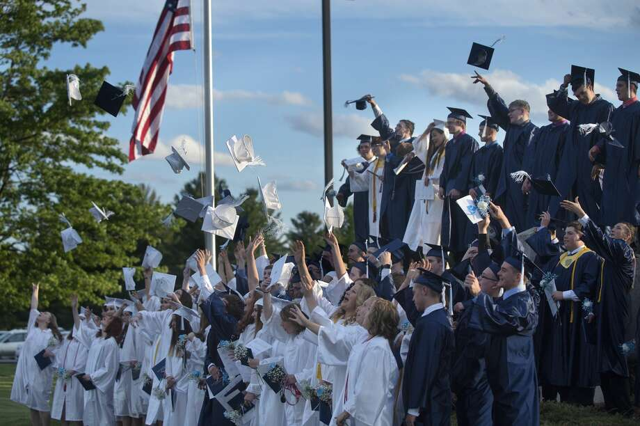Meridian Early College High School graduates toss up their mortar boards while having the class photo taken in front of the school Thursday evening. Photo: Brittney Lohmiller/Midland Daily News/Brittney Lohmiller