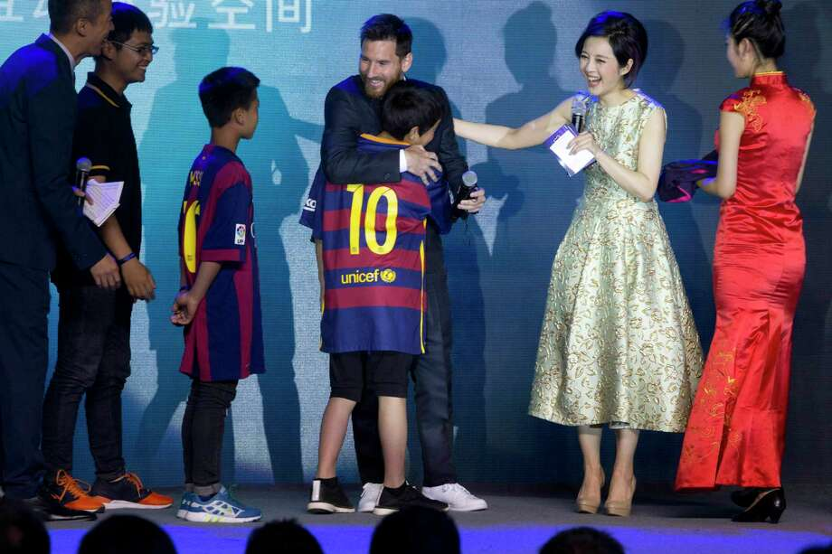 Barcelona's Lionel Messi, centre, hugs young footballers from a Chinese rural school during an event to launch the establishment of Messi Experience Park in Beijing, China, Thursday, June 1, 2017. The park to be completed within 2 years in eastern China will be based on football culture and promote the sports amongst China's youths. (AP Photo/Ng Han Guan) Photo: Ng Han Guan, STF / Copyright 2017 The Associated Press. All rights reserved.