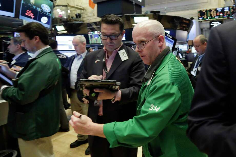 FILE - In a Friday, May 26, 2017 file photo, Kevin Walsh, right, moves between fellow traders as he works on the floor of the New York Stock Exchange. Yet another sign that the job market continues to improve helped to lift stocks and interest rates on Thursday, June 1, 2017. The Standard & Poor's 500 index is on track for its first up day in three and is close to its record high. (AP Photo/Richard Drew, File) Photo: Richard Drew, STF / AP