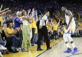 Fans react after Golden State Warriors' Kevin Durant hit a three-pointer in the fourth quarter during Game 1 of the 2017 NBA Finals at Oracle Arena on Thursday, June 1, 2017 in Oakland, Calif.