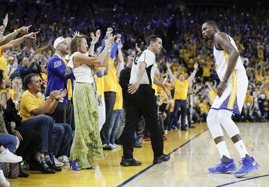 Fans react after Golden State Warriors' Kevin Durant hit a three-pointer in the fourth quarter during Game 1 of the 2017 NBA Finals at Oracle Arena on Thursday, June 1, 2017 in Oakland, Calif. Photo: Carlos Avila Gonzalez, The Chronicle