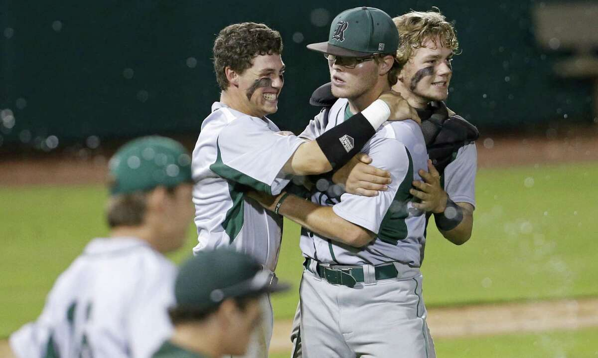 Reagan's Jake Hoggatt (center) is congratulated by teammates Grant Ellis (left) and Mac Papini after Game 1 of their Region IV-6A final series against Churchill Thursday June 1, 2017 at Nelson W. Wolff Municipal Stadium. Reagan won 4-0.