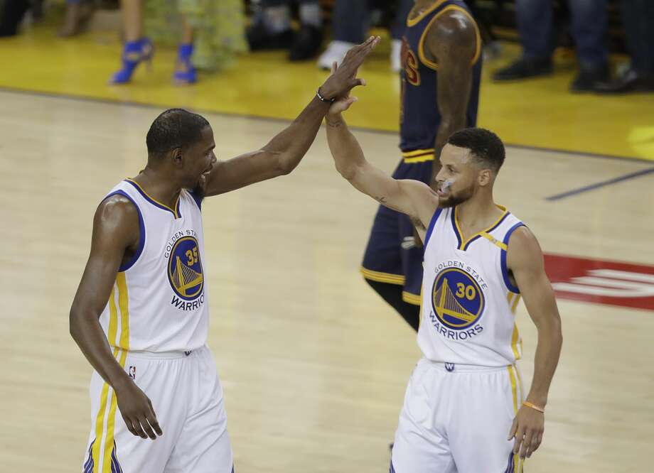 Golden State Warriors forward Kevin Durant (35) and guard Stephen Curry (30) react during the first half of Game 1 of basketball's NBA Finals against the Cleveland Cavaliers in Oakland, Calif., Thursday, June 1, 2017. (AP Photo/Marcio Jose Sanchez) Photo: Marcio Jose Sanchez/Associated Press