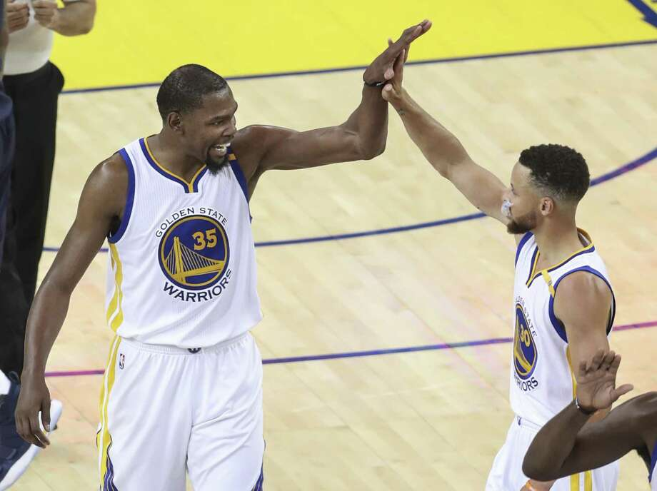 Golden State Warriors' Kevin Durant and Stephen Curry high five in the second quarter during Game 1 of the 2017 NBA Finals at Oracle Arena on Thursday in Oakland. Photo: Scott Strazzante / The Chronicle / online_yes