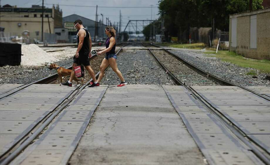 A couple and their dog walk past train tracks on Commerce near Sunset Station on Thursday, June 1, 2017. County Judge Nelson Wolff is thinking about a passenger rail line going from The Rim to Martin St. at Interstate 35, using existing freight line tracks owned by Union Pacific. (Kin Man Hui/San Antonio Express-News) Photo: Kin Man Hui /San Antonio Express-News / ©2017 San Antonio Express-News