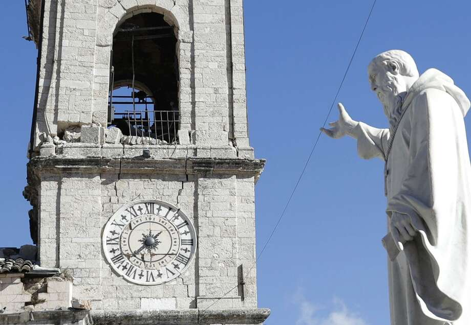 A statue of St. Benedict is backdropped by the damaged town hall bell tower in Norcia, central Italy, Italy, Monday, Oct. 31, 2016. The third powerful earthquake to hit Italy in two months spared human life Sunday but struck at the nation's identity, destroying a Benedictine cathedral, a medieval tower and other beloved landmarks that had survived the earlier jolts across a mountainous region of small historic towns. (AP Photo/Gregorio Borgia) Photo: Gregorio Borgia / Associated Press / Copyright 2016 The Associated Press. All rights reserved.