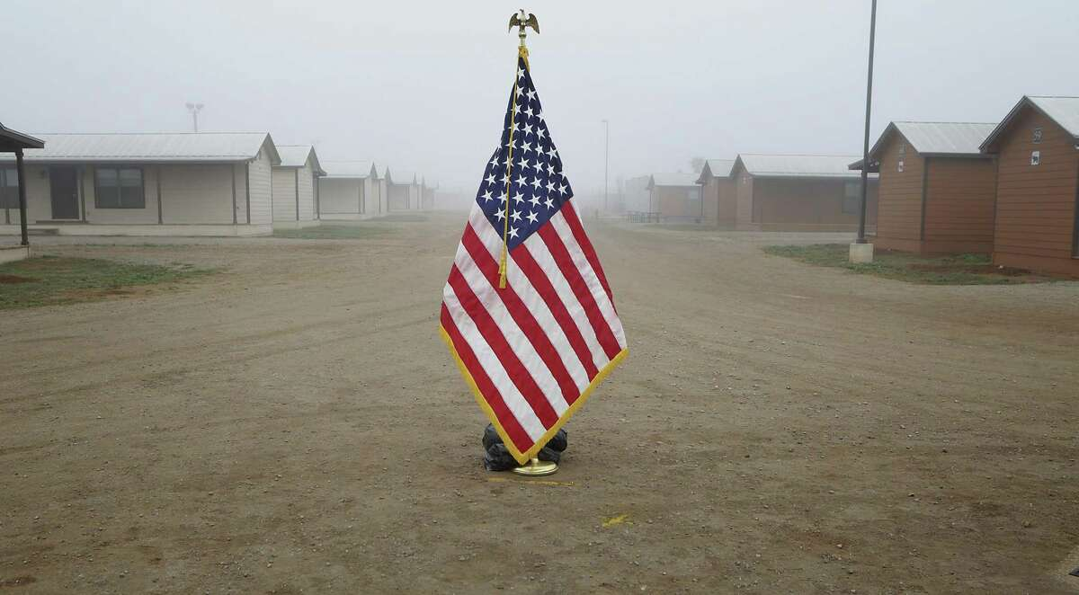 """An American flag is set in the middle of the pathway, where Secretary of Homeland Security Jeh Johnson toured the new South Texas Family Residential Center, just outside Dilley, Texas. Detained immigrants that are currently being held in Artesia will begin arriving at the Dilley facility within the next two weeks. This pictured center, built as a """"man camp"""" for the oil and gas industry, is a temporary center that will be used until the new facility is completed. The new facility will accomadate 2400 individuals. Monday, Dec. 15, 2014."""