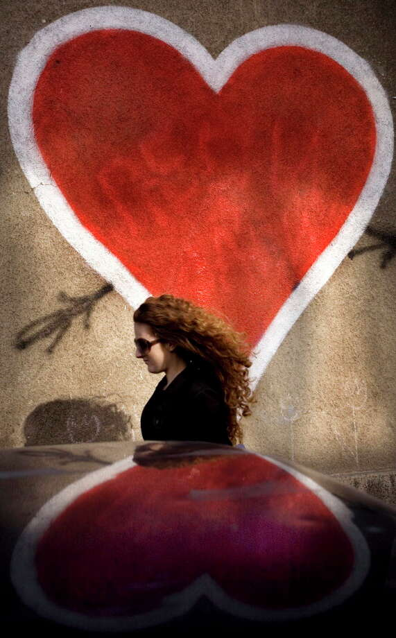 A woman passes a large Valentine's hearts drawn on a wall in the Bulgarian capital of Sofia. Bulgarians, who traditionally celebrate grape growing and wine making feastivals on Feb. 14, have begun to also mark  Valentine's Day since the Communist rule collapsed in the Balkan country in 1989. (AP Photo/Valentina Petrova) Photo: VALENTINA PETROVA, STR / AP