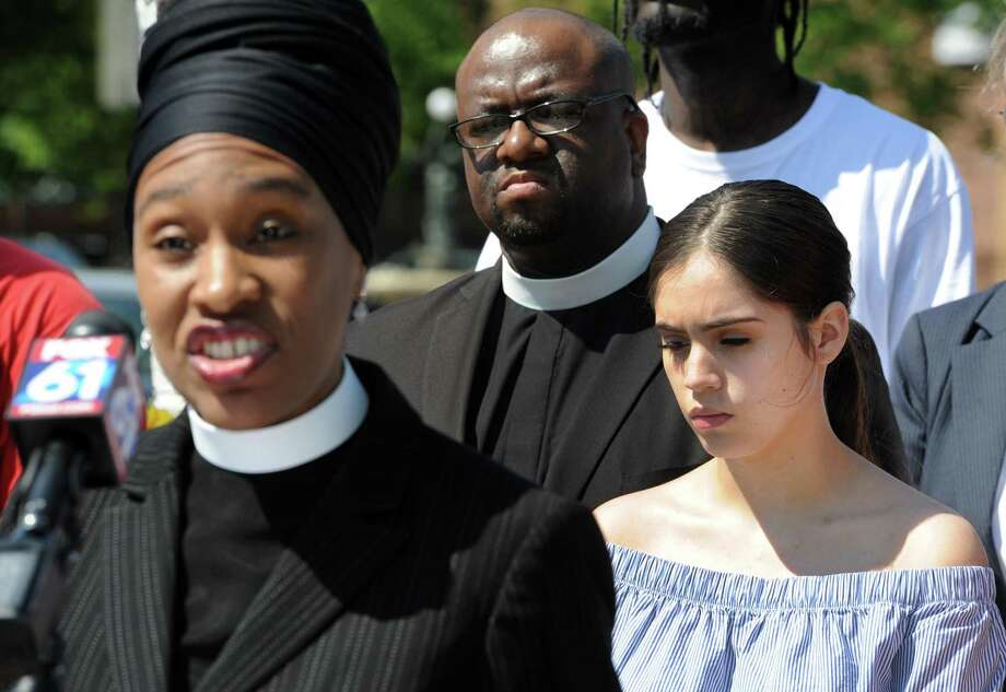 The Rev. Teddy Hickman-Maynard of Bethel AME Church, center, and Jayson Negron's half-sister Jazmarie Melendez, right, listens to The Rev. Bernadette Hickman-Maynard of Bethel AME Church speaks to others gathered at the site of Negron's shooting on Fairfield Avenue in Bridgeport, Conn. CONECT clergy and lay leaders called for a more public investigation during a press conference on Friday, June 2, 2017. Photo: Cathy Zuraw / Hearst Connecticut Media / Connecticut Post