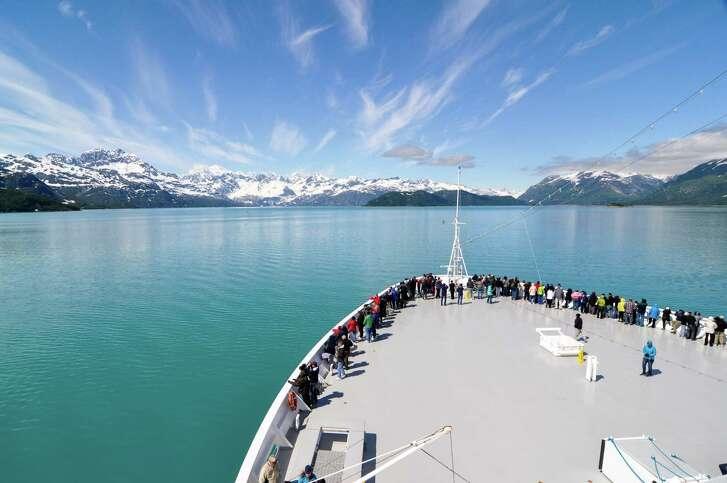 Holland America Line's MS Zaandam enjoys smooth sailing on a sunny day cruising through Glacier Bay National Park in Alaska.