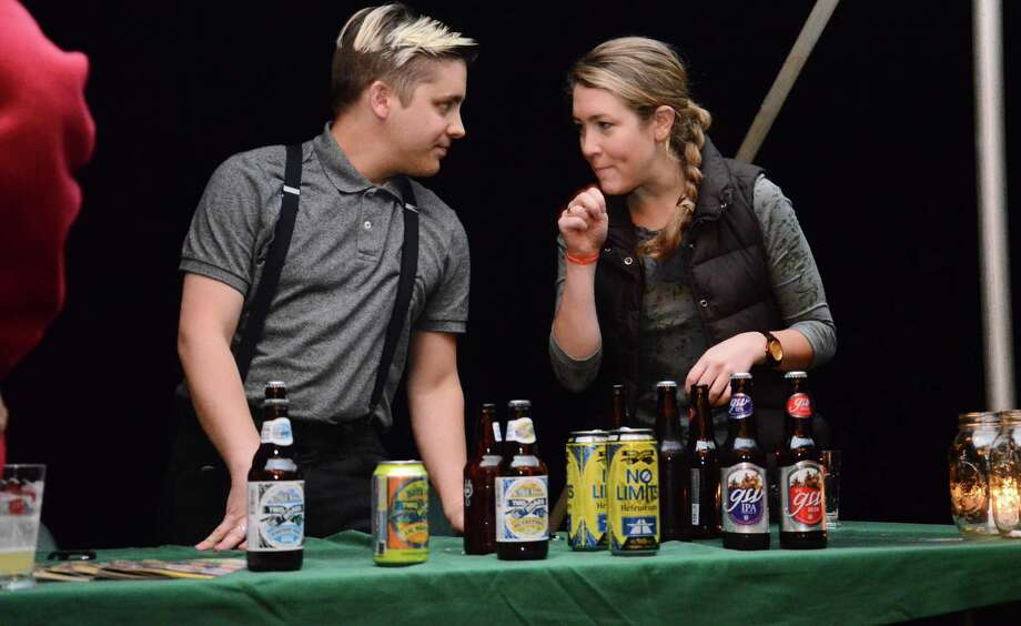 Dan Tazzioli and Isabel Lynch in October 2014 at the Two Roads and GW beer stand. Greenwich resident Todd Myers created GW Beer based on a recipe in a journal of George Washington. Photo: Nelson Oliveira / Nelson Oliveira / New Canaan News
