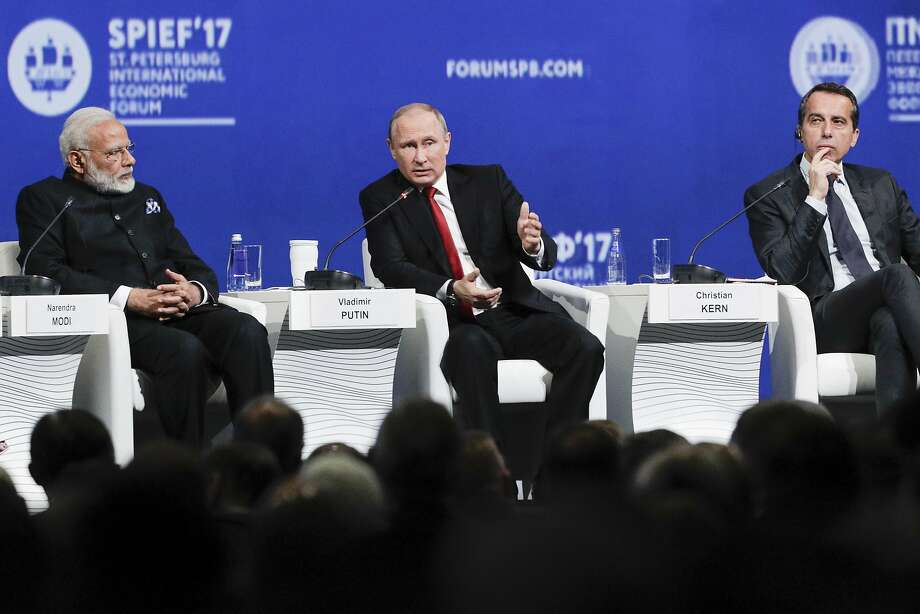 Vladimir Putin (center), flanked by Austrian Chancellor Christian Kern (left) and Indian Prime Minister Narendra Modi, speaks at the economic forum. Photo: Dmitry Lovetsky, Associated Press