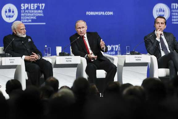 Russian President Vladimir Putin, center, answers a question at the St. Petersburg International Economic Forum in St.Petersburg, Russia, Friday, June 2, 2017. Austrian Chancellor Christian Kern, is on the left, India's Prime Minister Narendra Modi, is on the right. (AP Photo/Dmitry Lovetsky)
