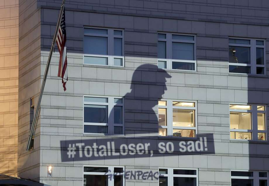 A Greenpeace banner showing U.S. President Donald Trump and the slogan '#TotalLoser, so sad!' is projected onto the facade of the U.S. Embassy in Berlin, Germany, Friday, June 2, 2017. Trump declared Thursday he was pulling the U.S. from the landmark Paris climate agreement, striking a major blow to worldwide efforts to combat global warming and distancing the country from its closest allies abroad. (AP Photo/Michael Sohn) Photo: Michael Sohn, Associated Press