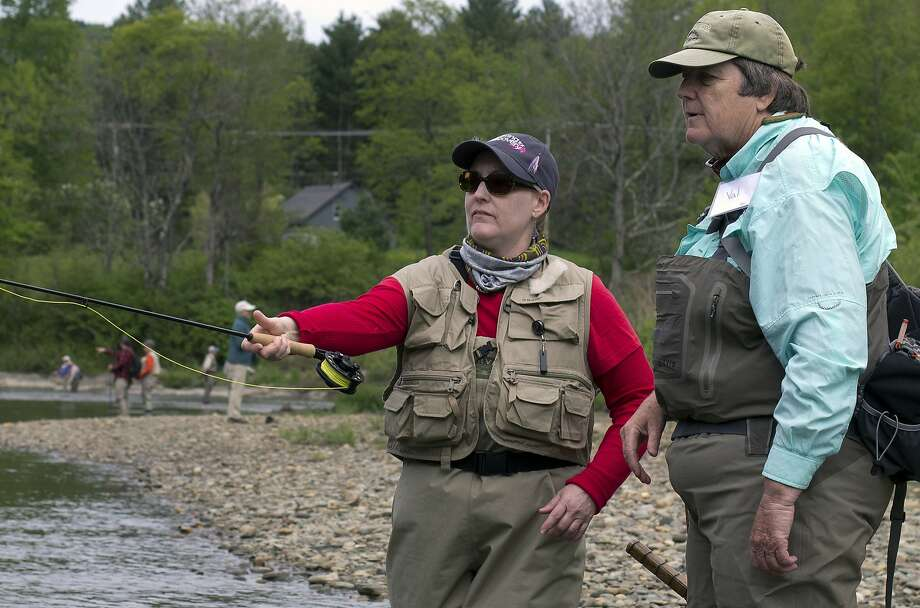 In this May 21, 2017 photo, Susan Cappucci, left, casts a line in the Little River in Moscow, Vt., with instruction from volunteer fly fishing guide Val Gardner, right. Cappucci was among a group of breast cancer survivors who participated in a retreat hosted by Casting for Recovery, a nonprofit organization created in 1996 to provide women with peer support, education and the therapeutic benefits of fly fishing. (AP Photo/Holly Ramer) Photo: Holly Ramer, Associated Press