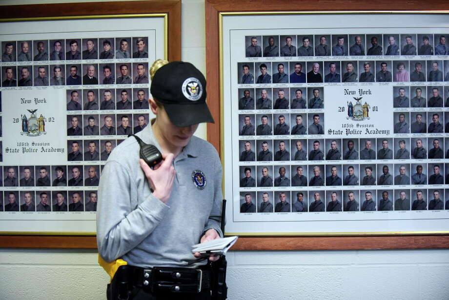 Photos of past New York State Police Academy graduates are seen on the wall at the academy as New York State Police Recruit Trooper Meghan Lohman takes part in a training scenario on Thursday, Feb. 2, 2017, in Albany, N.Y.   (Paul Buckowski / Times Union) Photo: PAUL BUCKOWSKI, Albany Times Union / 20039568A