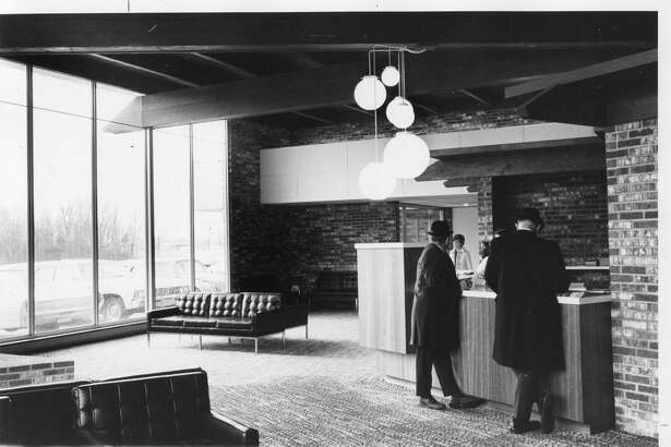Two men pause to check into the new Holiday Inn at the main desk in the lobby. They can be assured of reservations at any Holiday Inn in the country in a matter of seconds. January 1967