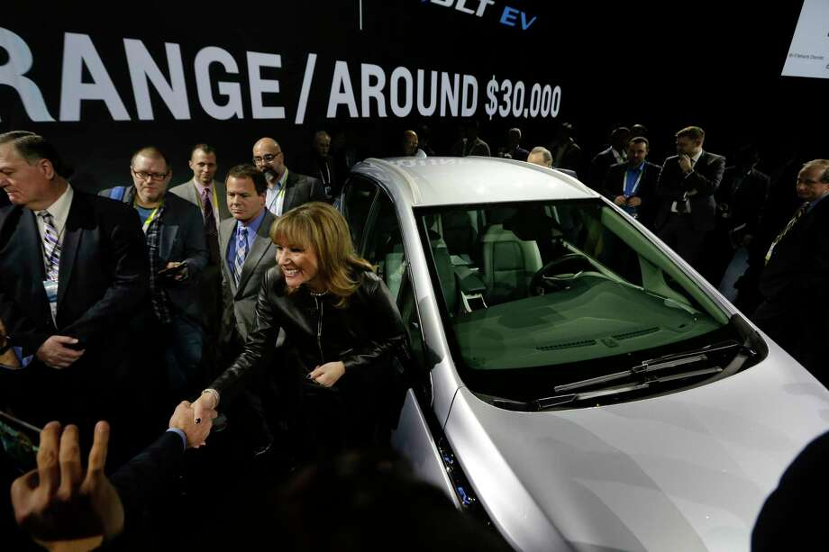 FILE - In this Wednesday, Jan. 6, 2016, file photo, General Motors Co. CEO Mary Barra stands next to the Chevrolet Bolt EV electric car at CES International in Las Vegas. Tesla and General Motors have a budding rivalry that could help determine whether Detroit or Silicon Valley sets the course for the future of the auto industry. Right now Wall Street is favoring the upstart led by flamboyant Elon Musk to the established icon headed by the more restrained Mary Barra. (AP Photo/Gregory Bull, File) Photo: Gregory Bull, STF / Copyright 2017 The Associated Press. All rights reserved.