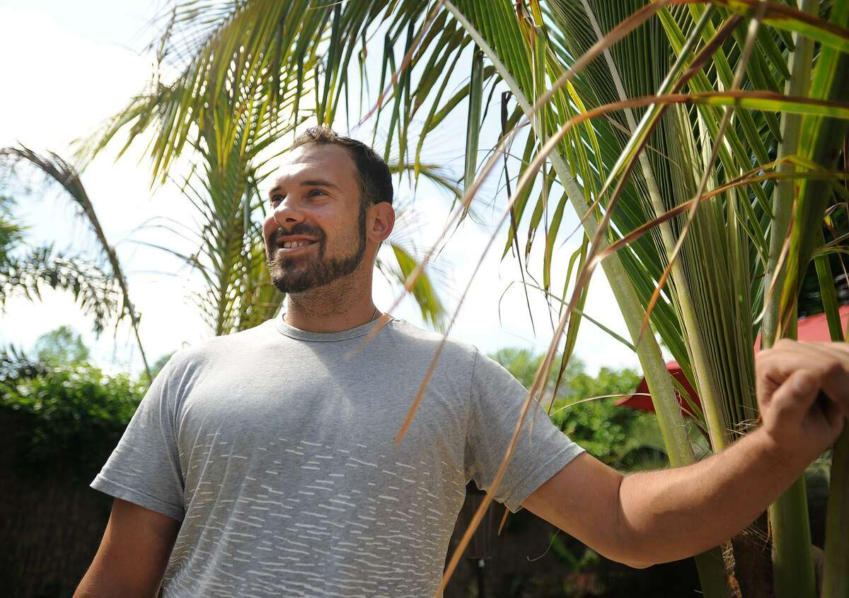 Brandon Hall, owner of CT Palm, a seasonal palm tree rental business, in his palm tree lined back yard in Fairfield on Wednesday.