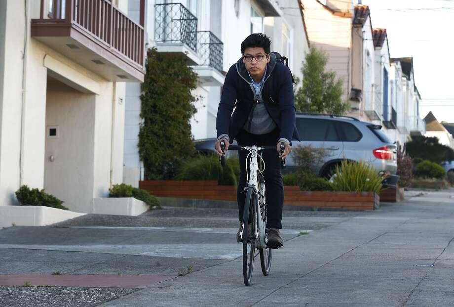 David Cruz Hernandez rides a bicycle near his Sunset District home. Photo: Paul Chinn, The Chronicle