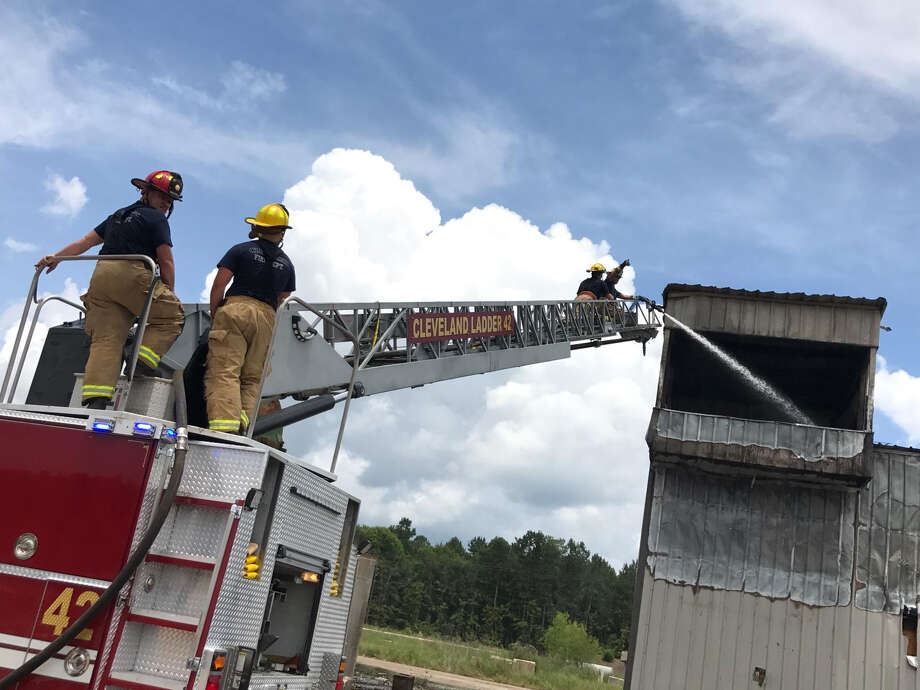 Cleveland firefighters pour water onto a fire at an old sawmill north of town. The fire was intentionally set by a company hired to clear the land of all the remainders of the former sawmill. Photo: Submitted