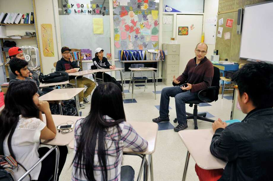 Albany High School English teacher, Brian Huskie, right, talks with high school refugee students, from background to foreground, Beya Paw, Blah Hsae, Soe Aung, Saad Bene Jamiel, Uma Siwakoti, Say Htoo, and Shar Reh on Tuesday, May 17, 2016, in Albany, N.Y.  (Paul Buckowski / Times Union) Photo: PAUL BUCKOWSKI / 40036636A