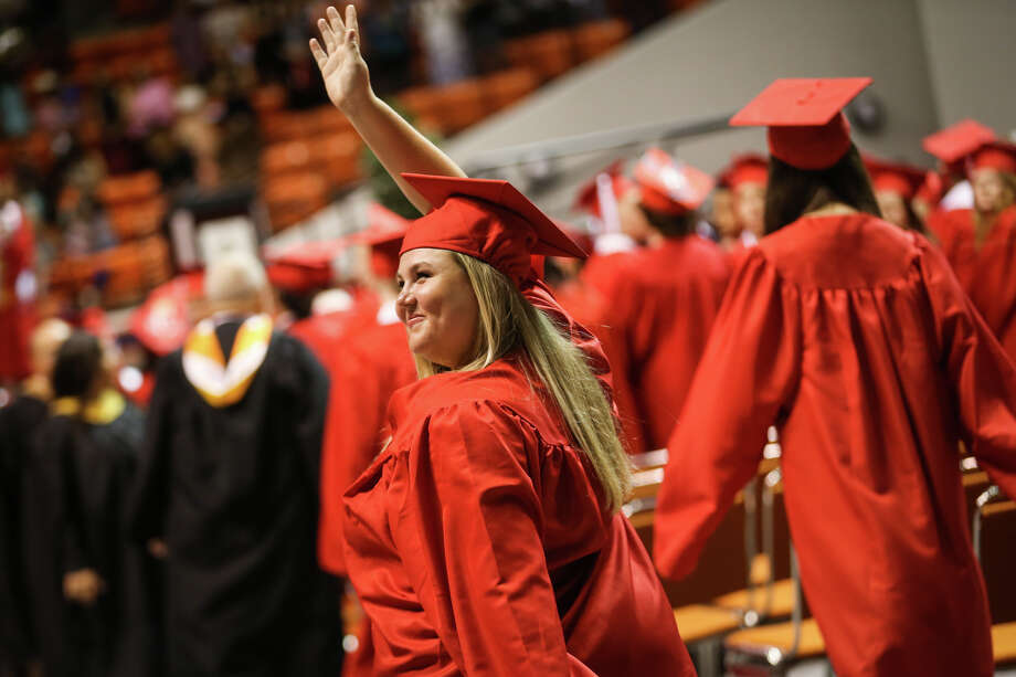 Graduates wave at family and friends in the stands during the processional of the Splendora High School commencement ceremony on Sunday, May 28, 2017, at Sam Houston State University. Photo: Michael Minasi, Staff Photographer / © 2017 Houston Chronicle
