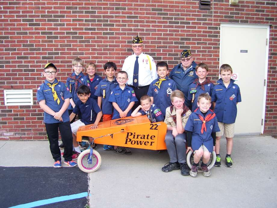 Scout members of Pack #3582 huddle around their new gift form American Legion Post 197. On hand to present the cart was this year's Post Commander Bob Winkel and member Bob Sopczynski. After the donation, several Cub Scouts tried the cart on a small hill near the donation site.