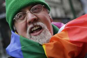 FILE - In this Monday, March 17, 2014 file photo, artist Gilbert Baker, designer of the Rainbow Flag, is draped with the flag while protesting at the St. Patrick's Day parade in New York. Baker, creator of the flag that has become a widely recognized symbol of gay rights, has died at age 65. His death was reported Friday, March 31, 2017 to the New York City medical examiner�s office. (AP Photo/Mark Lennihan)