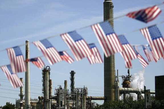 "In this April 30, 2008 file photo, American flags are seen near the Shell refinery, in Martinez, Calif. On Weds., Nov. 14, 2012, California�s largest greenhouse gas emitters will for the first time begin buying permits in a landmark ""cap-and-trade"" system meant to control emissions of heat-trapping gases and spur investment in clean technologies. The program is a key part of California�s 2006 climate-change law, AB32, a suite of regulations that dictate standards for cleaner-burning fuels, more efficient automobiles and increased use of renewable energy. (AP Photo/Ben Margot, File)"