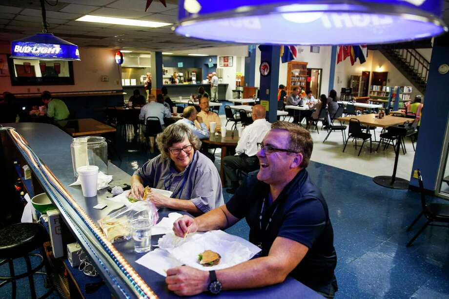 Port chaplains Lacy Largent, left, and Tom Edwards share a laugh over a burger from the restaurant at the Tellepsen location of the Houston International Seafarers' Center, which is moving to a smaller building. Photo: Michael Ciaglo, Staff / Michael Ciaglo
