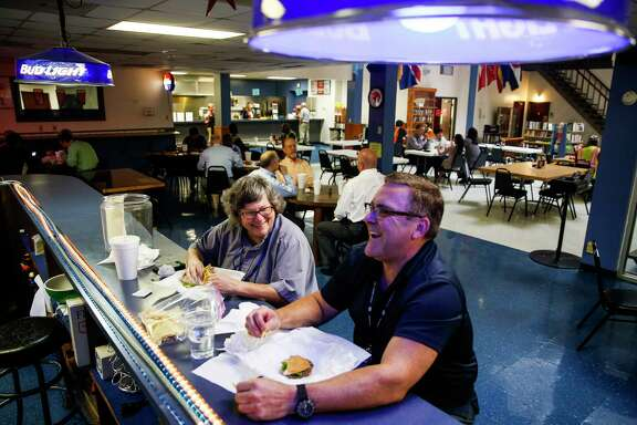 Port chaplains Lacy Largent, left, and Tom Edwards share a laugh over a burger from the restaurant at the Tellepsen location of the Houston International Seafarers' Center, which is moving to a smaller building.