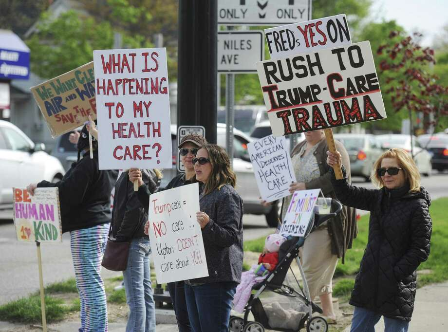 People gather outside of Rep. Fred Upton's St. Joseph, Mich., office May 3 to protest his support of the health care bill. One of the major issues is the House's treatment of pre-existing conditions. Photo: Don Campbell /Associated Press / The Herald-Palladium
