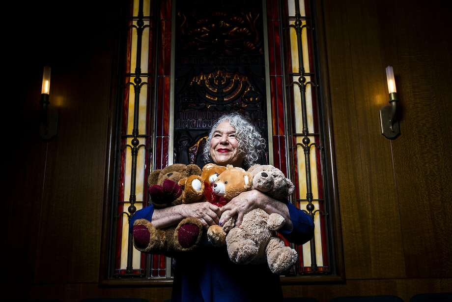 Samantha Grier, founder and president of Caring for Children, a nonprofit that has sent therapeutic tools to emotionally deprived children since 1986, holds teddy bears at Congregation Emanu-El's temple in San Francisco. Photo: Stephen Lam