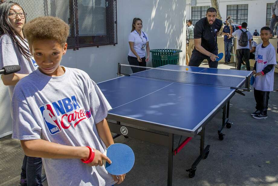 "Above: Warriors center JaVale McGee (right) plays ping pong with students at Oakland's Westlake Middle School, where, below, Warriors GM Bob Myers (left), NBA Commissioner Adam Silver and Mayor Libby Schaaf christen a ""learn and play zone."" Photo: Santiago Mejia, The Chronicle"