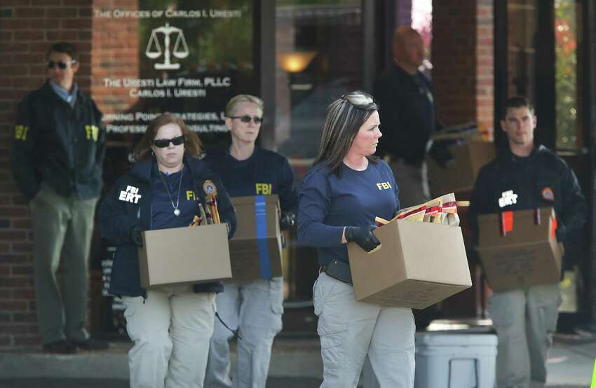 FBI agents carry boxes of evidence to a government truck after the FBI raided the office State Senator Carlos Uresti in San Antonio, Tx, on Thursday, Feb. 16, 2017.