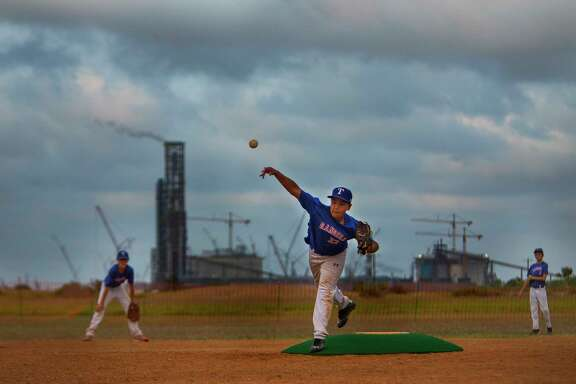 With the stack from the VoestAlpine iron plant and construction of Cheniere's new LNG export facility behind him, 11 year-old Eli Garza pitches during a game with his little league team, the Rangers, Tuesday, May 16, 2017, at Simpson Park in Portland. The teams are currently playing on temporary fields near NorthShore Country Club while new city fields are built near Gregory-Portland High School. (Mark Mulligan / Houston Chronicle)