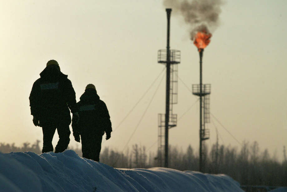Two workers walk near a gas flare-off at the Yukos owned Mamontovskoye oil-field in the Khanty-Mansy region of the Russian Federation, Friday, December 17, 2004. Russia's state-owned OAO Rosneft said it will take over the main production unit of OAO Yukos Oil Co., the exporter of 11 percent of the nation's petroleum. Photographer: Dmitry Beliakov/Bloomberg News. Photo: DMITRY BELIAKOV